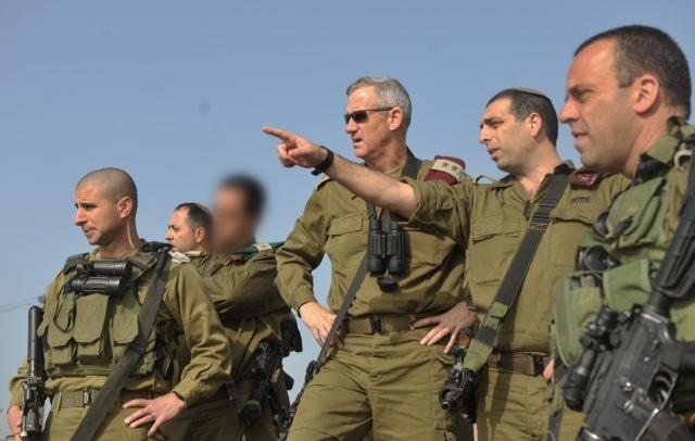 le général Ofek Buchris, deuxième à droite, avec le chef d'Etat major d'alors Benny Gantz pendant une visite du nord d'Israël, quand Buchris dirigeait la division Bashan de l'armée israélienne, en 2014. (Crédit : unité des portes-paroles de l'armée israélienne)
