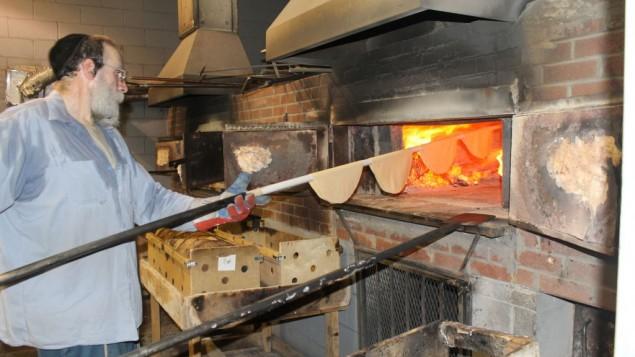 Il faut environ 20 secondes dans un four à bois et à charbon à 1300° pour cuire la matzah shmoura à la perfection. (Crédit : Uriel Heilman)