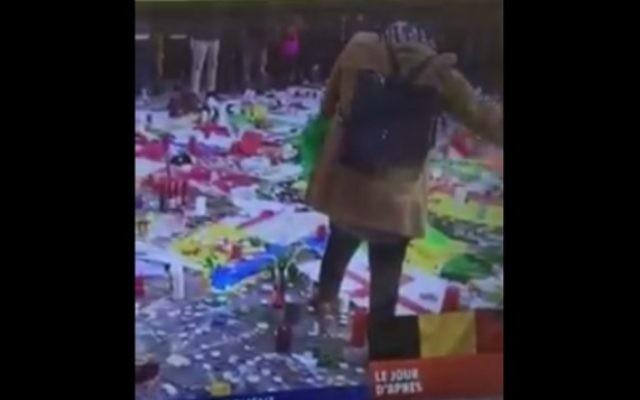 Une femme avec un hijab est vue en train d'enlever un drapeau israélien de la place de la Bourse de Bruxelles, à un mémorial improvisé après les attentats suicide qui ont tué plus de 30 personnes, le 23 mars 2016. (Crédit : capture d'écran Facebook)