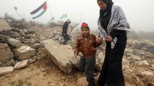 L'épouse de Raid Masalmeh, un Palestinien qui a poignardé deux Israéliens à mort à Tel Aviv, marche dans les débris de sa maison après sa démolition, près du village de Dura, en Cisjordanie, le 23 février 2016. (Crédit : AFP / HAZEM BADER)