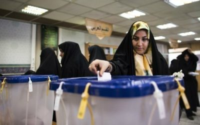 Une iranienne vote pour les élections parlementaires  dans un bureau de vote de Massoumeh dans la ville sainte de Qom, à 130 kilomètres au sud de Téhéran, le 26 février 2016. (Crédit : Behrouz Mehri/AFP)