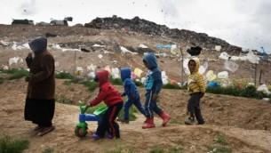 Des enfants bédouins israéliens de la tribu Tarabin jouent dans leur village bédouin non reconnu, près de la décharge de Dudaim (arrière-plan), près de la ville de Rahat, dans le sud du pays, le 7 février 2016. (Crédit : Menahem Kahana/AFP,)