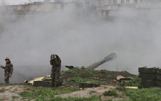 Des militaires arméniens de l'armée d'autodéfense du Nagorny-Karabakh en train de tirer un obus d'artillerie en direction des forces azéries de leurs positions dans la ville de Martakert dans la région azerbaïdjanaise de Nagorny-Karabakh, le 3 avril 2016. (Crédit : Vahram Baghdasaryan/Photolure/AFP)
