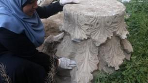 Un archéologue palestinien inspecte les artefacts retrouvés pendant la construction d'un centre commercial à Gaza Ville, le 4 avril 2016. (Crédit : AFP/Mohammed Abed)