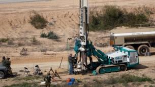 Sur cette photo d'illustration du 10 février 2016, des soldats israéliens surveillent une machine permettant de creuser des trous dans le sol côté israélien de la frontière avec la bande de Gaza pour détecter des tunnels utilisés par des groupes terroristes palestiniens qui prévoient d'attaquer Israël. (Crédit : Menahem Kahana/AFP)