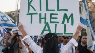 """Une femme avec un panneau """"Tuez-les tous"""" pendant un rassemblement de soutien à un soldat accusé d'avoir tué un attaquant palestinien neutralisé en mars à Hébron, le 19 avril 2016. (Crédit : Jack Guez/AFP)"""