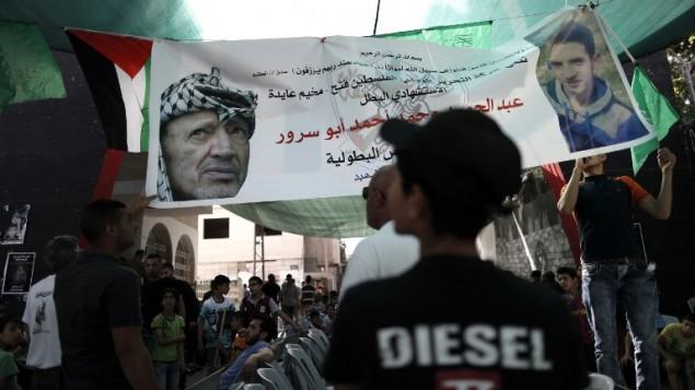 Des Palestiniens se rassemblent sous une bannière montrant le terroriste du bus de Jérusalem du 18 avril, Abdel Hamid Abu Srour, et Yasser Arafat, au camp d réfugiés al-Ayda le 21 avril 2016. (Crédit : AFP PHOTO/THOMAS COEX)