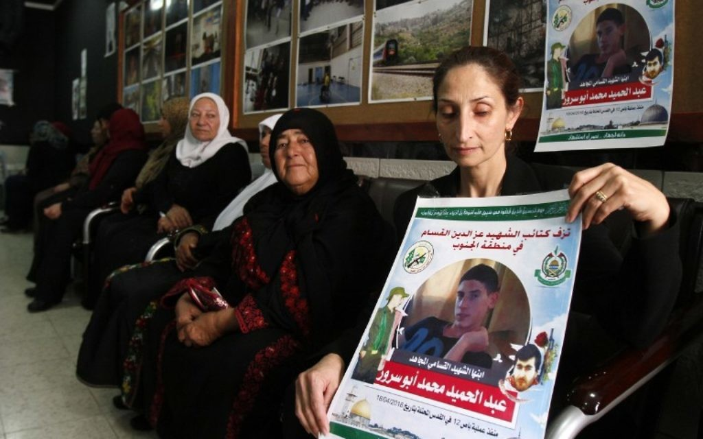 Azhar Abu Srour, la mère d'Abdel Hamid Abu Srour, 19 ans (sur l'affiche), qui a mené un attentat suicide dans un bus de Jérusalem le 18 avril, porte le deuil avec les membres de sa famille et reçoit des condoléances au centre Al-Ruwad du camp de réfugiés d'al-Ayda, le 22 avril 2016. (Crédit : AFP PHOTO / MUSA AL SHAER)