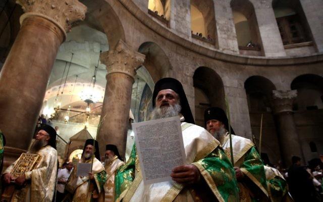 Des prêtres grecs orthodoxes lors de la procession pascale du dimanche des rameaux à l'église du Saint-Sépulcre dans la vieille cité de Jérusalem, le 24 avril 2016. (Crédit photo : AFP PHOTO / GALI TIBBON)