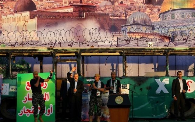 Ismail Haniyeh, du Hamas, (deuxième à gauche) participe à un rassemblement anti-israélien à Gaza-Ville, le 28 avril 2016, devant un fond dépeignant le bus de Jérusalem qui a explosé. (Crédit photo : AFP/Mohammed Abed)
