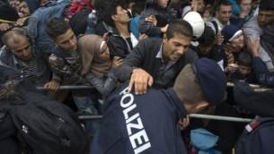 Des centaines de migrants luttent pour monter à bord d'un train à Nickelsdorf, du côté autrichien de la frontière entre l'Autriche et la Hongrie, le 11 septembre 2015. (Crédit : AFP/Joe Klamar)