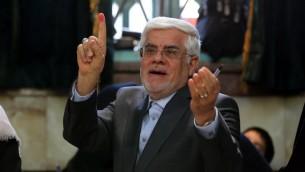 La tête de liste iranienne de la coalition réformiste pour les élections législatives de 2016, Mohammad Reza Aref, montre son doigt après avoir voté à Téhéran, le 26 février 2016. (Crédit : AFP/ATTA KENARE)