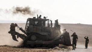 Un bulldozer israélien D9 le long de la frontière sud d'Israël avec la bande de Gaza, après des frappes aériennes israéliennes sur a bande de Gaza le 10 juillet 2014. (Crédit : Jack Guez/AFP)