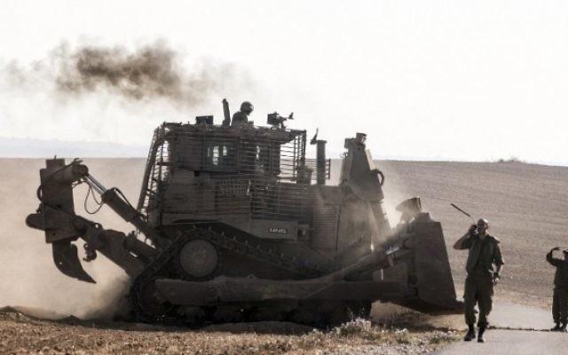 Un bulldozer israélien D9 le long de la frontière sud d'Israël avec la bande de Gaza, après des frappes aériennes israéliennes sur la bande de Gaza, le 10 juillet 2014 (Crédit : Jack Guez/AFP)