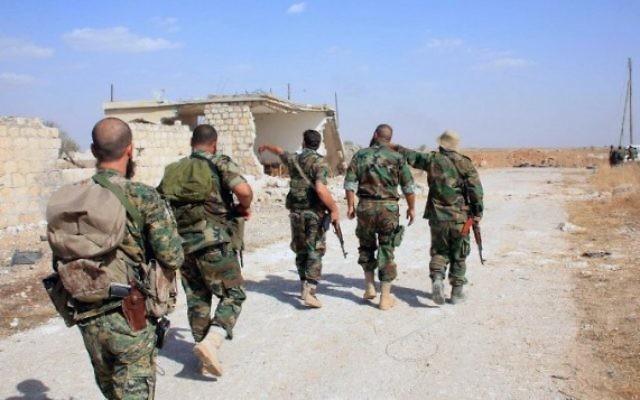 Archive : des soldats du régime syrien marchent sur une route dans une zone située autour de l'aéroport militaire Kuweires, dans la province orientale d'Alep, le 16 octobre 2015. (Crédit : AFP / George Ourfalian)