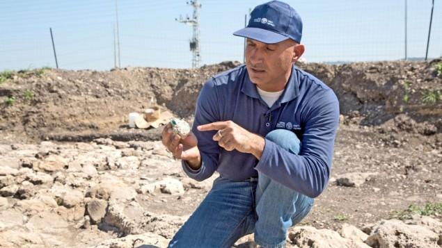 Le directeur des fouilles Abdel Al-Salam Said, examine l'un des morceaux de verre retrouvé dans la zone de fouille. (Crédit : Shmuel Magal, autorisation de l'Autorité israélienne des Antiquités)