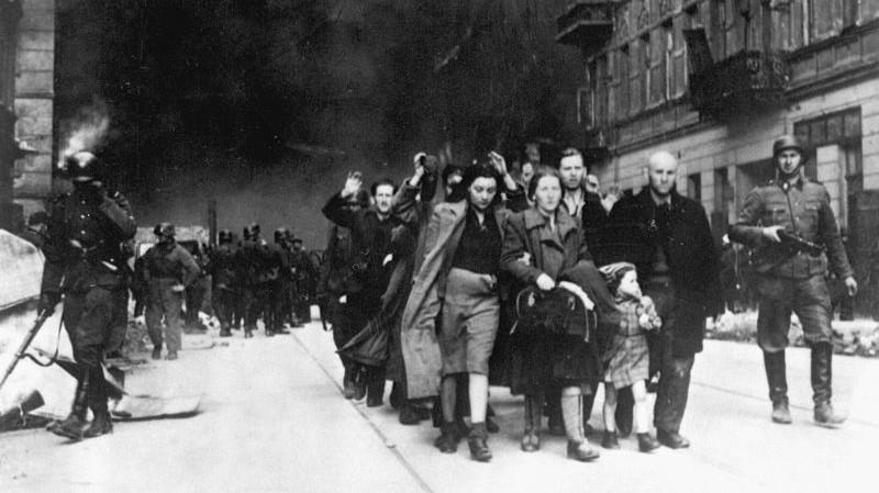 Les Juifs du ghetto de Varsovie conduits par des soldats allemands à un point de rassemblement pour la déportation vers les camps de la mort, en 1943 (Crédit : Domaine public)