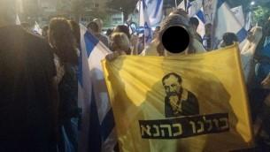 """Un adolescent avec un drapeau """"Nous sommes tous Kahane"""" pendant un rassemblement de soutien à un soldat accusé d'avoir tué un attaquant palestinien neutralisé en mars à Hébron, le 19 avril 2016. (Crédit : Judah Ari Gross/Times of Israel)"""