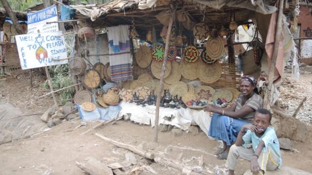 Une habitante et son fils près de leur étal pur touristes à l'entrée du village de Wolleka, un village juif abandonné à Gondar, Éthiopie, devenu une attraction touristique majeure, le 24 avril 2016.(Melanie Lidman/Times of Israel)