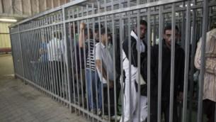 Des travailleurs palestiniens attendent pour passer un checkpoint depuis la ville de Ramallah, en Cisjordanie, vers Israël, le 4 juin 2013. (Crédit photo : Yonatan Sindel/Flash90)