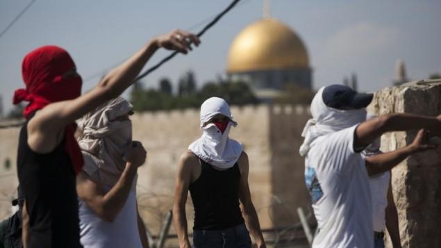 Des Palestiniens jetant des pierres sur des policiers israéliens (non visibles) à Jérusalem Est (Crédit : Yonatan Sindel/Flash90)