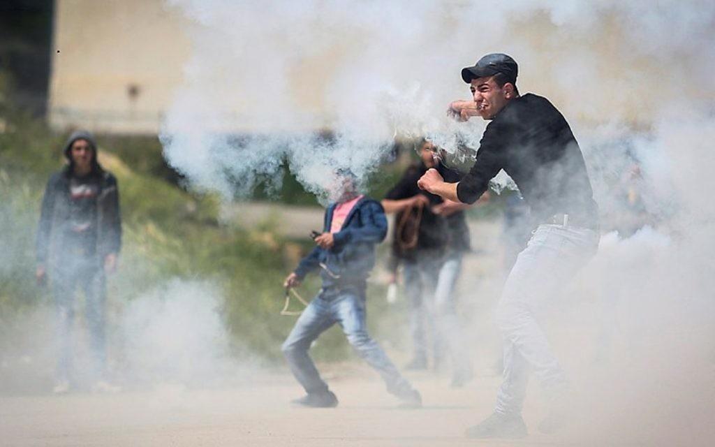 """Des Palestiniens manifestent devant les forces de sécurité israéliennes pendant la """"Journée de la Terre"""", devant la prison Ofer, gérée par les Israéliens, près de Betunia, en Cisjordanie, le 30 mars 2016. (Crédit : Flash90)"""