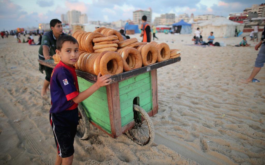 Des jeunes enfants qui vendent du pain sur la plage de Gaza le 13 juin 2015 dans la ville de Gaza (Crédit : Christopher Furlong / Getty Images via JTA),