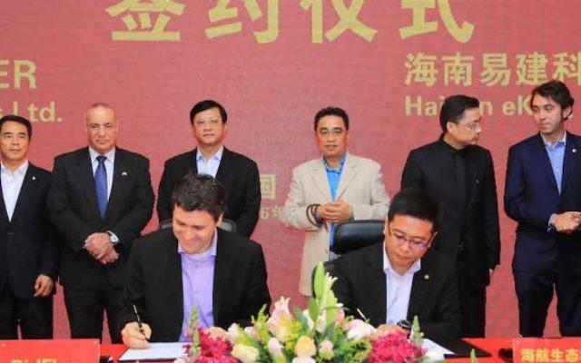 Asaf Gendler, CEO de la start-up israélienne Bidflyer (au premier plan à gauche) et Kevin Yu, COO de Hainan Eco-Tech Group (au premier plan à droite), pendant la signature d'un accord de partenariat. (Crédit : autorisation)