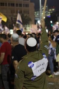 """Un soldat place Rabin à Tel Aviv pendant un rassemblement de soutien à un soldat accusé d'avoir tué un attaquant palestinien neutralisé en mars à Hébron, le 19 avril 2016. Il est écrit """"Pas un meurtrier, un héros !' sur sa veste militaire. (Crédit : Judah Ari Gross/Times of Israel)"""