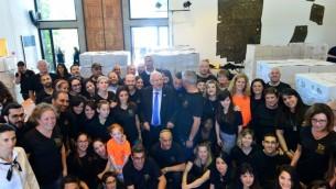 Le président Reuven Rivlin, entouré des volontaires de Leket Israël et de l'équipe du bureau du président, a participé à l'emballage de colis de nourriture pour Pessah, à la résidence présidentielle de Jérusalem, le 20 avril 2016. (Crédit : Kobi Gideon/GPO)