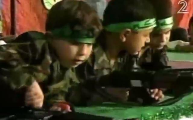Des petites garçons palestiniens jouent avec de fausses armes dans une pièce de théâtre jouée à Gaza dans le cadre du Festival de Palestine pour les enfants et l'éducation, en avril 2016. (Crédit : capture d'écran Deuxième chaîne)
