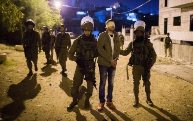 Illustration. Des soldats israéliens arrêtent un Palestinien dans le camp de réfugiés de Duhaisha, près de Bethléem, en Cisjordanie, le 8 décembre 2015. (Crédit : Nati Shohat/Flash90)
