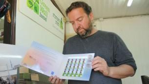 Guy Barnes montre au Times of Israel les timbres publiés par le gouvernement israélien pour l'exposition 2015 à Milan (Crédit : Melanie Lidman/Times of Israel)