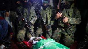 Des membres des Brigades Ezzedine al-Qassam près du corps de Marwan Maarouf, 27 ans, pendant ses funérailles à Khan Yunis, dans le sud de la bande de Gaza, le 9 février 2016. Maarouf a été tué par l'effondrement d'un tunnel dans la bande de Gaza. (Crédit : Abed Rahim Khatib/Flash90.