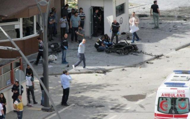 Des policiers étudient les débris devant le siège de la police à Gaziantep, une ville du sud est de la Turquie, après un attentat le 1er mai 2016. (Crédit : AFP/Ilhas News Agency)