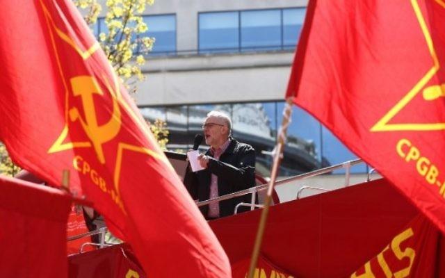 Jeremy Corbyn (au centre), chef du parti d'opposition britannique, le Parti travailliste, pendant un discours donné pendant un rassemblement du 1er mai depuis le toit d'un bus à deux étages entre des drapeaux du Parti communiste (marxiste-léniniste) anglais à Londres, le 1er mai 2016. (Crédit : AFP/JUSTIN TALLIS)
