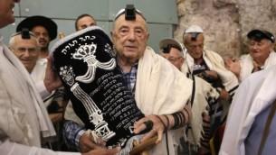 Des dizaines de survivants juifs de l'Holocauste portent talith et tefilin en portant un rouleau de Torah après leur bar mitzvah au mur Occidental, dans la Vieille Ville de Jérusalem, le 2 mai 2016. (Crédit : AFP/Menahem Kahana)