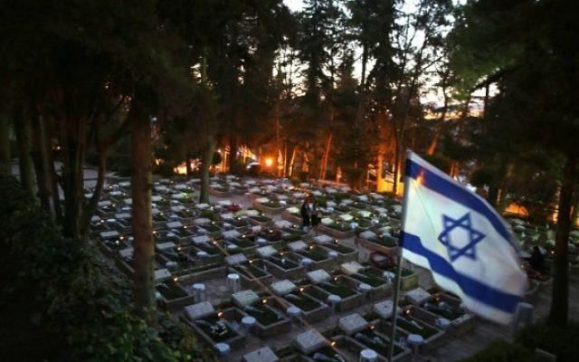 Une Israélienne visite la tombe d'un  proche au cimetière militaire du mont Herzl, à Jérusalem, au début du Jour du Souvenir, commémorant les soldats israéliens tombés, le 10 mai 2016. (Crédit : AFP PHOTO / MENAHEM KAHANA)