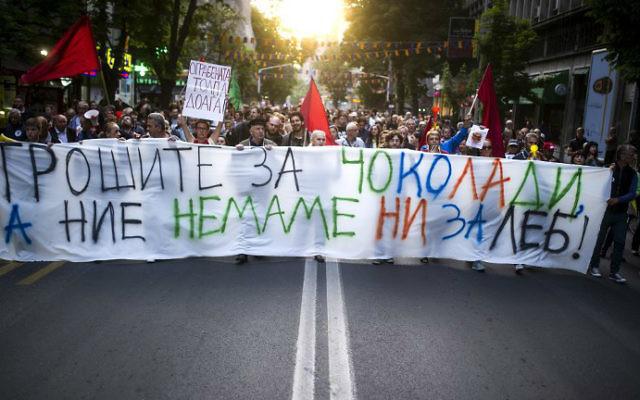 """Des manifestants marchent derrière la banderole sur laquelle on peut lire """"Vous achetez du chocolat alors que nous n'avons même pas assez de pain"""", à Skopje, en Macedoine, le 10 mai 2016 (Crédit : Robert Atanasovski/AFP)"""
