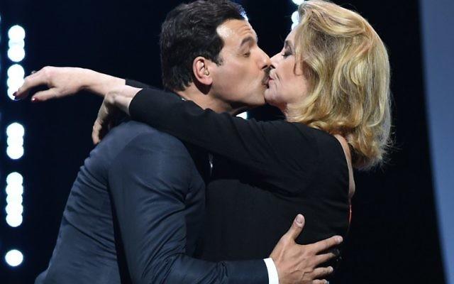 Catherine Deneuve embrasse Laurent Lafitte le 11 mai 2016, à l'ouverture du 69e festival de Cannes. (Crédit : AFP / ALBERTO PIZZOLI)