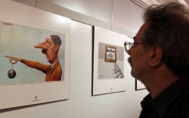 Un Iranien observe une caricature montrant Hitler, lors de la deuxième exposition internationale de dessins et caricatures sur l'Holocauste, à Téhéran, le 14 mai 2016. (Crédit : AFP/Atta Kenare)