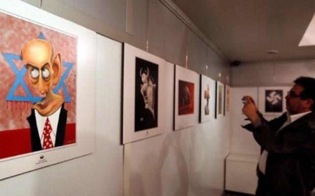 Un Iranien prend en photo un dessin exposé au concours international de caricatures sur l'Holocauste à Téhéran, le 14 mai 2016. (Crédit : AFP PHOTO / ATTA KENARE)