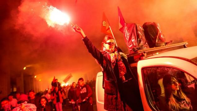 Des manifestants allument des fusées éclairantes et agitent des drapeaux tout en marchant dans une rue lors d'une manifestation anti-gouvernementale à Skopje, en Macédoine, le 16 mai 2016. (Crédit : Robert Atanasovski / AFP)