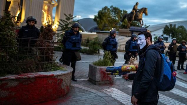 """Un manifestant portant un masque utilise un pistolet à eau pour pulvériser de la peinture colorée sur la façade du bâtiment du ministère des Affaires étrangères, devant le cordon de police, lors d'une manifestation anti-gouvernementale à Skopje, en Macédoine, le 16 mai 2016. Ces deux dernières années, la Macédoine a connu une série de manifestations anti-gouvernementales surnommée """"la révolution de couleur"""". (Crédit : Robert Atanasovski / AFP)<br />"""