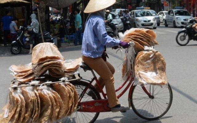 Un vendeur de rue sur son vélo dans le centre de Hanoï, au Vietnam, le 17 mai 2016. Illustration. (Crédit : AFP PHOTO/HOANG DINH NAM)