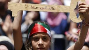 Une Palestinienne brandit une clé symbolisant les clés des maisons abandonnées par les Palestiniens en 1948, pendant un rassemblement de commémoration de la 68e Nakba, à Ramallah, le 17 mai 2016. (Crédit : AFP PHOTO / ABBAS MOMANI)