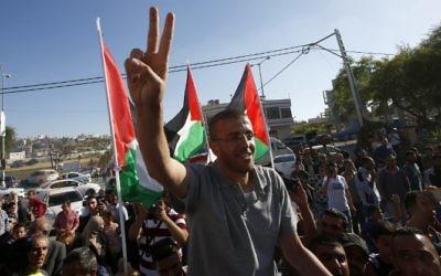 Le journaliste palestinien emprisonné, Mohammed al-Qiq, fait le symbole de la victoire alors qu'il arrive dans son village de Dura, au sud de la Cisjordanie, après avoir été libéré de la prison israélienne de Nafha, le 19 mai 2016 (Crédit : AFP/ HAZEM BADER)