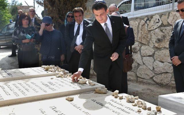 Le Premier ministre français Manuel Valls (C) visite les tombes de Jonathan, Arie et Gabriel Sandler, qui ont été tués en mars 2012 dans une attaque terroriste contre une école juive dans la ville française de Toulouse, au cimetière de Givat Shaul à Jérusalem le 23 mai 2016. (Crédit : Menahem Kahana/AFP)