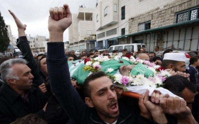 Funérailles d'Abdel Fattah al-Sharif, terroriste palestinien qui a été abattu par un soldat israélien alors qu'il était au sol, désarmé et blessé. Des centaines de personnes ont assisté aux funérailles, et son corps était enveloppé d'un drapeau du Hamas, à Hébron, le 24 mars 2016. (Crédit : AFP/Hazem Bader)