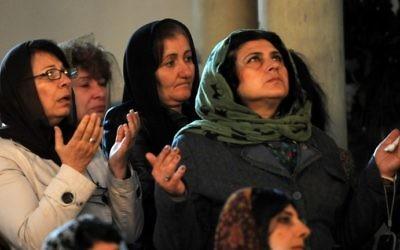 Des femmes prient durant un service religieux à la cathédrale d'Etchmiadzin, à l'extérieur d'Erevan, le 23 avril 2015, avant la cérémonie de canonisation pour les Martyres du génocide arménien (Crédit : Karen Minasyan/AFP)